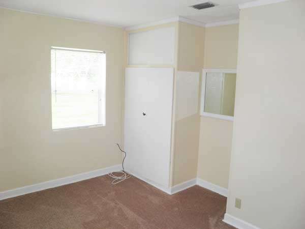 Bedroom 2 has built-in closet with storage above, recessed nook with mirror and two windows with blinds. (Room size: 13' x 9.5'.)