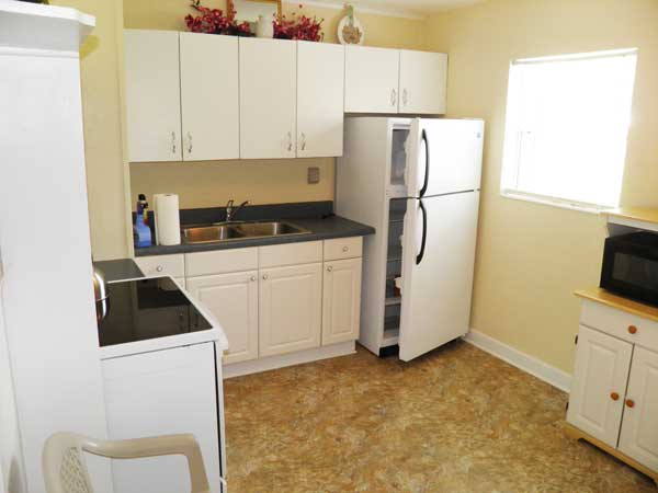 Bright eat-in kitchen with electric flat-top range/oven, refrigerator, microwave oven. (Room size: 13.5' x 10'.)
