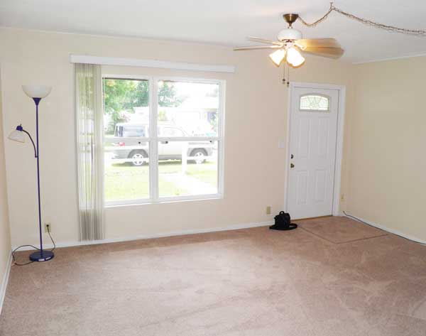 The living room overlooks front yard and car port. (Room size: 15.5′ x 13.5′)