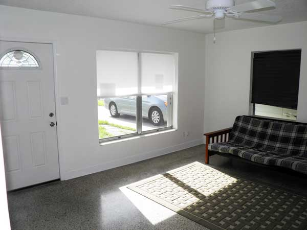 Bright living room features custom built-in shelving, serving bar from kitchen and windows onto carport and front yard.