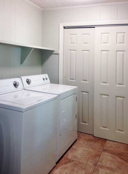 New laundry room with washer & dryer has lots of storage and tile throughout