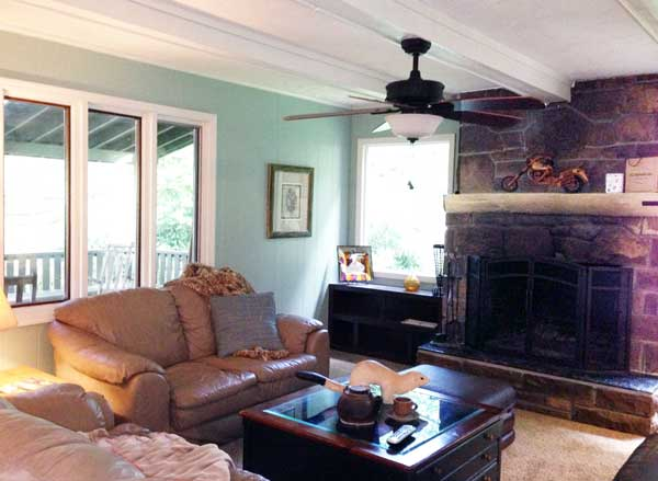 Cozy living room features beam ceilings, large stone fireplace and lots of windows