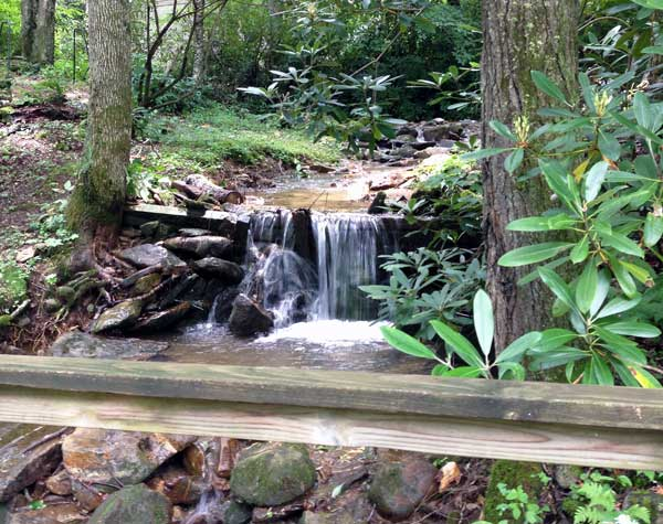Wooden bridge next to waterfall leads to back deck of home