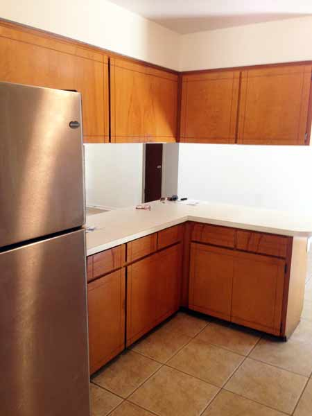 Bright open-plan kitchen with lots of cabinets, gas range/oven, refrigerator, breakfast bar. Kitchen size: 10' x 11'.