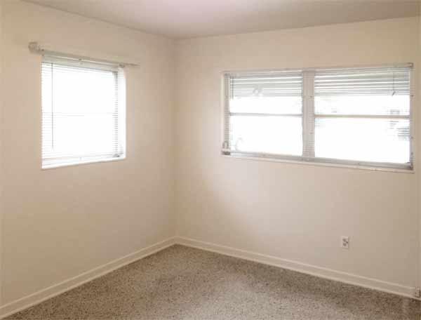 Private master bedroom (photo 1) windows face onto carport and side yard, terrazzo floors. Room size: 11' x 14'.